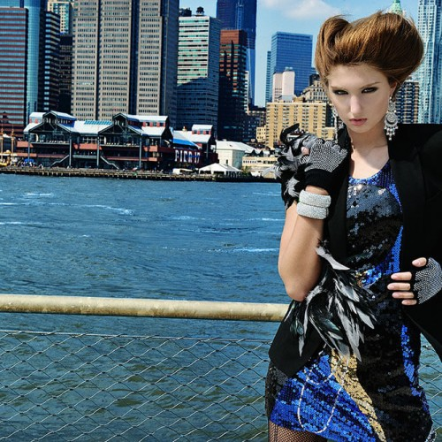 Model posing with a unique haircut and a city backdrop