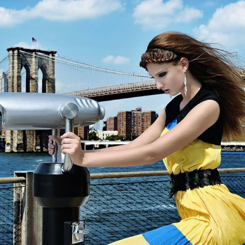 Model with long hair and braids with a bridge as the backdrop